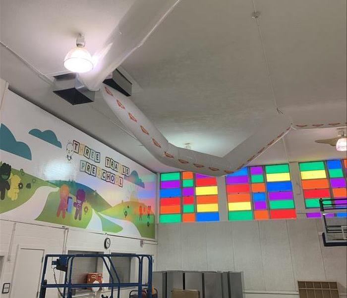 the upper part of the wall and ceiling of a colorful preschool with a large plastic tube set up through the vents