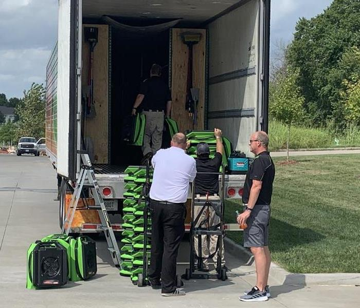 a team of guys unloading green air movers from a semi truck