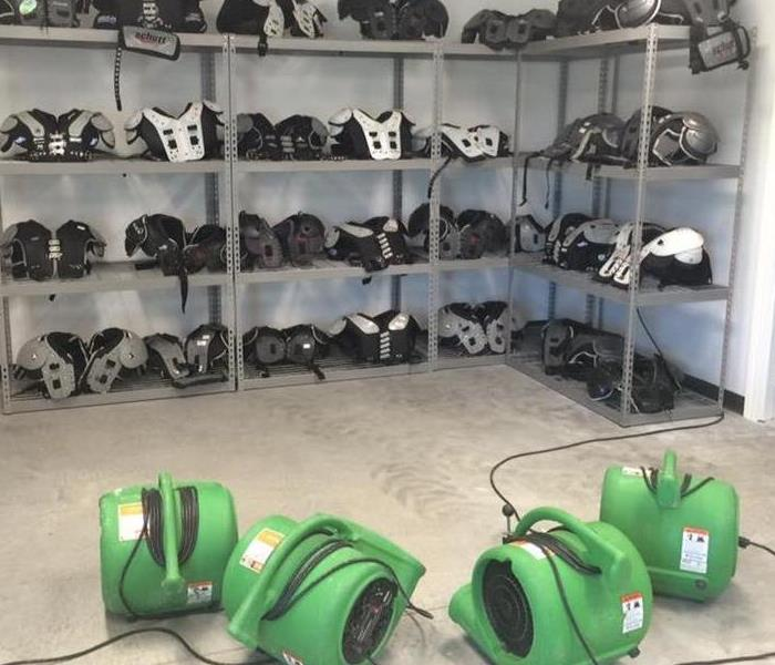 a room full of football equipment on shelves